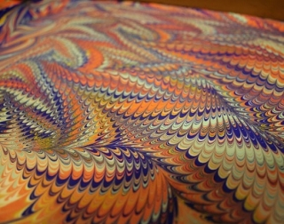 Multi-coloured marbled paint in purples, blues and oranges.