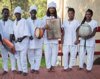 A group of musicians in white robes look at camera