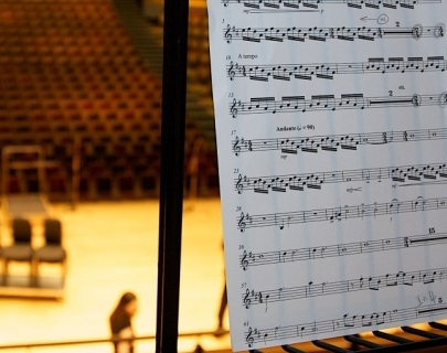A sheet of music on a stand, with a concert hall in the background