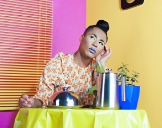 A person sits at a table, with a plate of food in front of them, in a brightly coloured room.