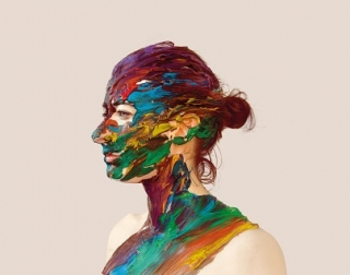 A woman in profile. Her face, neck and chest has been covered with streaks of multi-coloured paint.