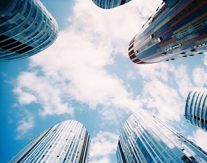 A photograph taken looking up to a blue sky, with cylindrical glass buildings all around