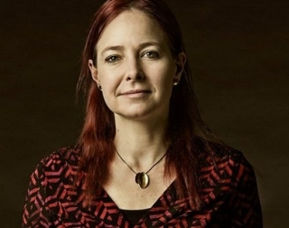 A woman with red hair smiles at the camera, standing in front of a black background