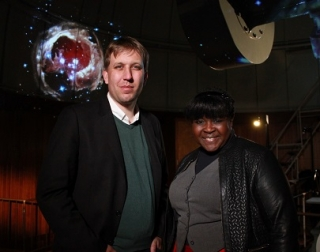 A man and a woman smile at the camera with space images behind them.