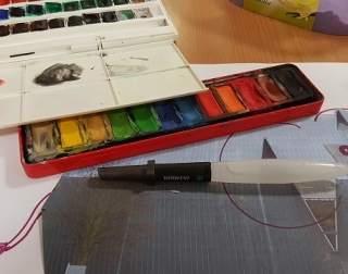 An open box of paints sits on a table, with paper and other art materials