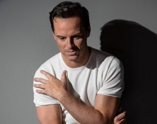 A man in a white t-shirt sat in front of a wall, looking down with his arm across his chest