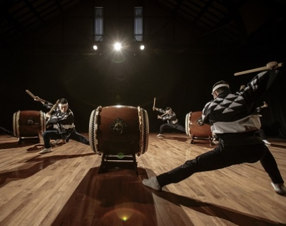 Three Kodo Drummers playng their drums on stage