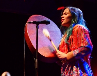 Lady with eyes closed plays a drum