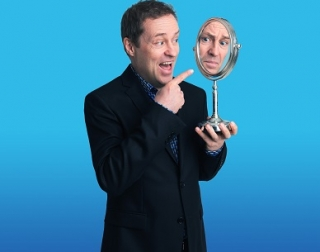 Man laughs and points to his reflection in a mirror