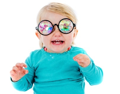 A baby with blonde hair wears a green jumper and a pair of multi-coloured glasses