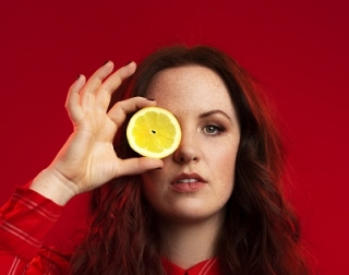 Woman looks at camera whilst holding a lemon over her eye