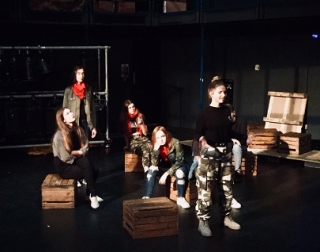 A group of young performers stand and sit on crates on a dark stage