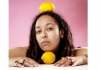 A person rests their chin on a lemon, looking at the camera, with another lemon resting on their head.