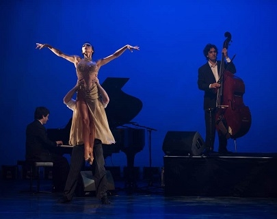 Two tango dancers pose in front of piano and double bass player with a deep blue background