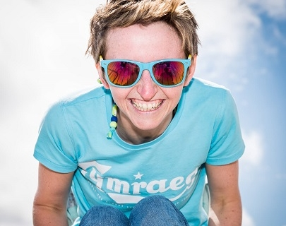 Woman in blue top and sunglasses smiles at camera