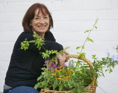 Lady in black top smiles with plants in a basket
