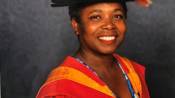 Director of Warwick Arts Centre, Doreen Foster smiles with graduation robes on