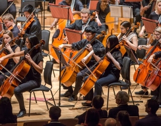 Cello players on stage, all dressed in black