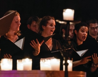 A choir surrounded by glowing candles
