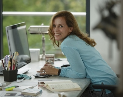 A woman with long hair, wearing a light blue shirt, leans on her desk with her hands over her keyboard and smiles at the camera