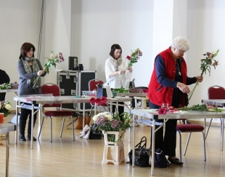 Three participants stand behind tables, arranging bunches of flowers