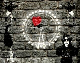 A brick wall with a white ferris wheel painted on it, and figures in black and white.