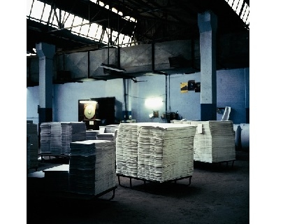 A photograph of the interior of a factory, with piles of paper sat on pallets