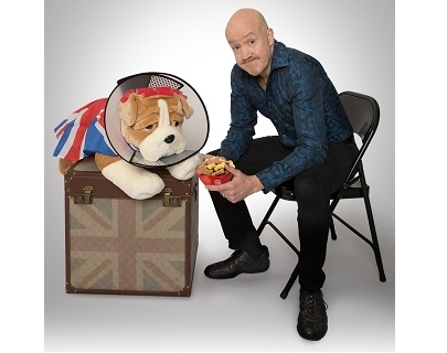 A man sits on a chair next to a chest which has a toy bulldog on top of it