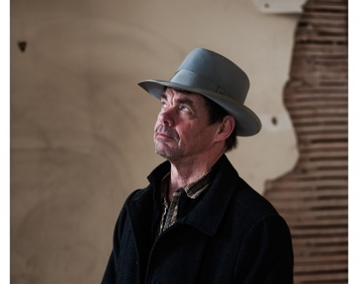 A man in a black jacket and a grey hat looks up and to the left