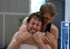 Two men perform stage combat. One has his arm wrapped around the other's neck.