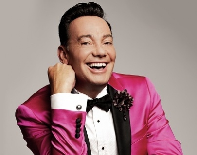 A man with dark hair, wearing a bright pink and black jacket, white shirt and black bow tie, smiles at the camera