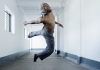 A performer jumps and twists in the air in a white and grey corridor. They are wearing grey trousers and a grey hood.