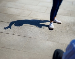 A person swearing trainers stands on paving slabs, creating a shadow of their legs and feet
