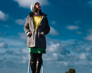 A woman in a coat and a hat stands on a metal ladder, looking at the stars.