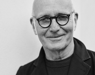 Black and white. A man wearing glasses smiles at the camera.
