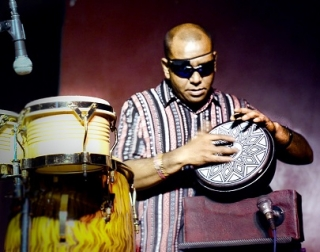 A man in dark glasses plays a patterned drum onstage.