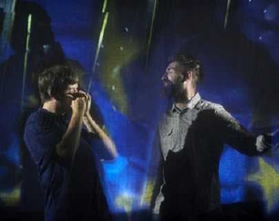 Two musicians in front of an abstract blue background.