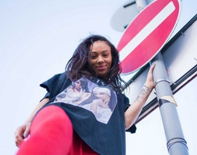 Low angle shot of a woman holding a street sign in red trousers and black top.