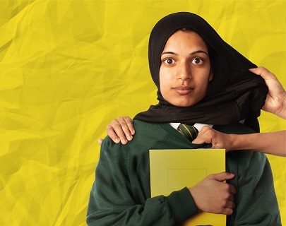 A girl in a school uniform holds her book and looks at the camera. Hands grab at her jumper and pull at her hijab.
