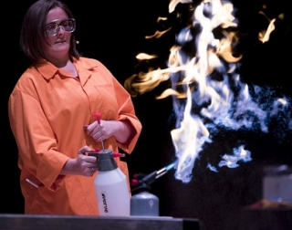 A woman in an orange science lab coat and protective goggles carrying out an experiment