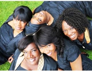 Five black women gathered on grass