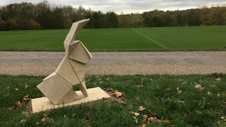 An origami hare set in the middle of a green field.