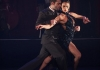 A man and woman tango dancing in black costumes