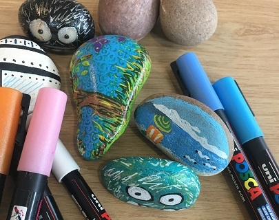 A selection of coloured pens and painted rocks on a table.