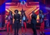 5 performers stand onstage and sing into microphones against a colourful background