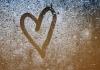 A heart drawn on a misty glass window.