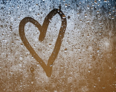 A heart drawn on a misty glass window.