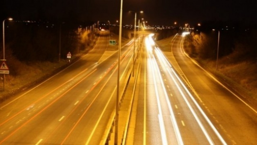 An image of a busy main road, with beams of light from car headlights.