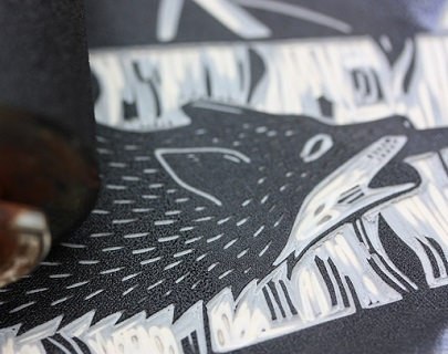 A linocut of a wolf in black ink