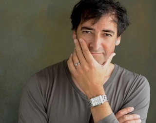 Alistair McGowan wears a grey shirt, looks into the camera and touches his face.